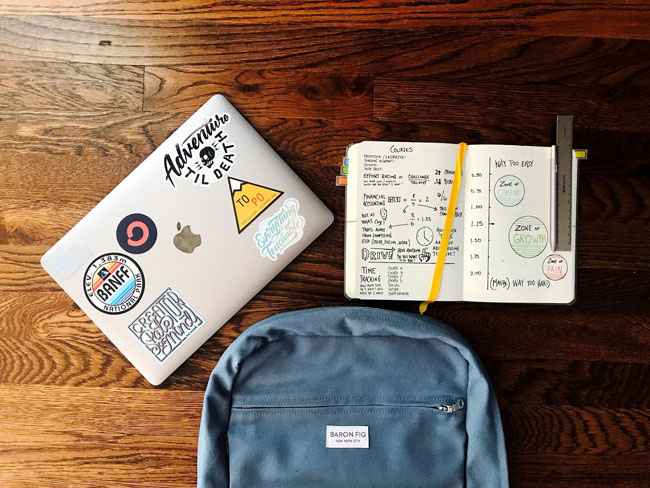 On a desk rests a backpack, a notebook, and a laptop computer.