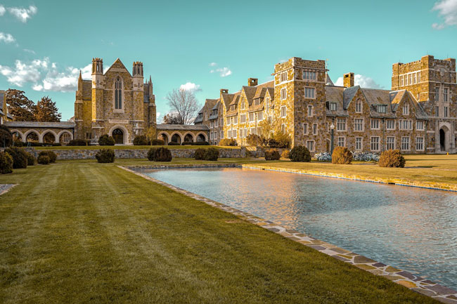 College campus and brick buildings with grassy lawn and reflection pool