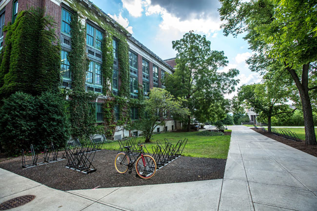 A college campus with ivy growing on buildings and rows of bike racks