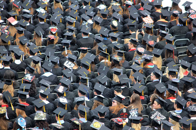 A crowd of graduates wearing hats and robes all sit together