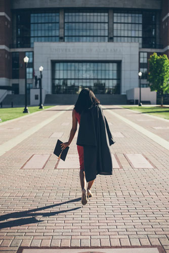 a college graduate walks across campus