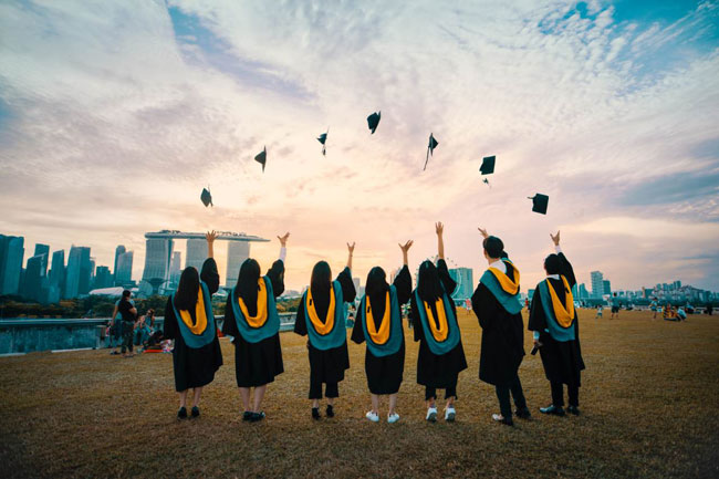 A group of students stands on a hillside tossing their graduation caps into the air