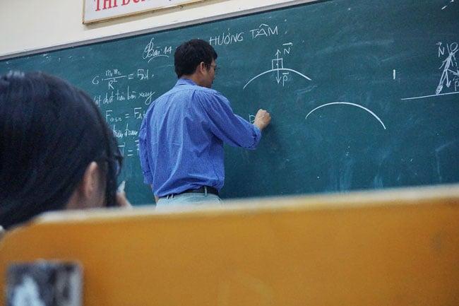 A teacher stands at a chalkboard writing