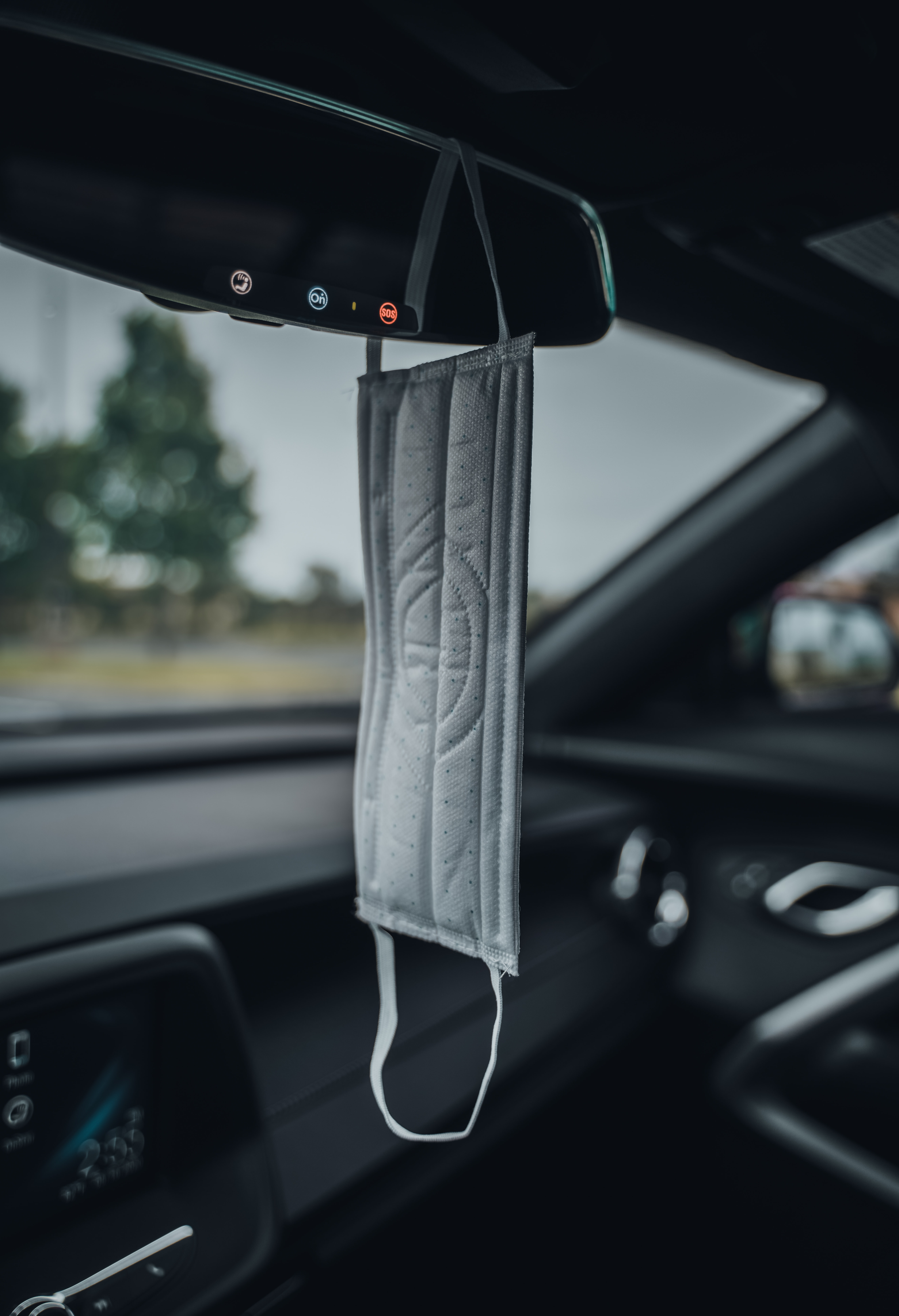 face mask hanging from car rearview mirror