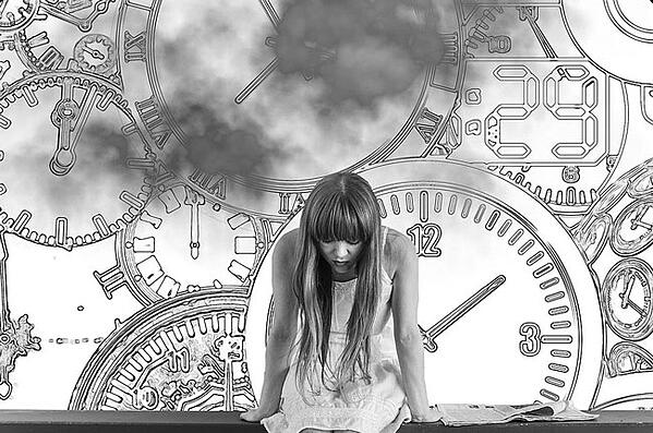 Woman waiting in front of wall filled with clocks