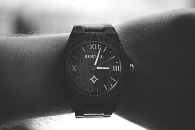 a man looks at the time on his wristwatch