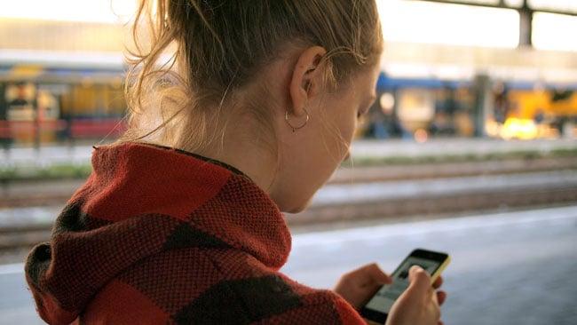 girl in plaid hoodie looking at her phone