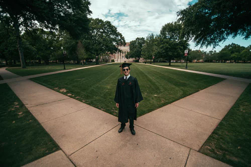 a graduate stands on campus