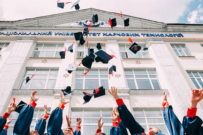 Students raise their hands and toss their graduation caps into the air
