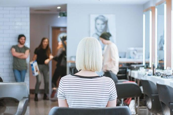 woman sitting in char in hair salon