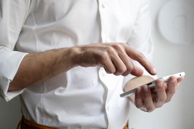 man in white shirt holding white phone