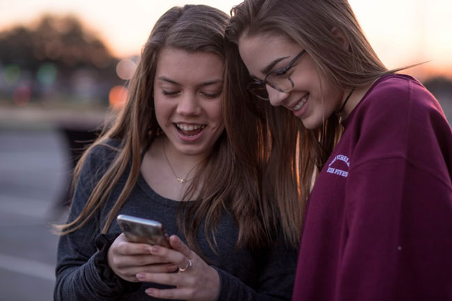 two students use a smartphone