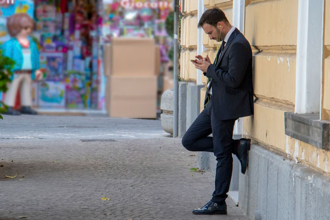 man standing and sending a text