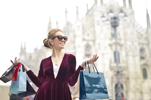 Smiling woman holding shopping bags outside of a large building