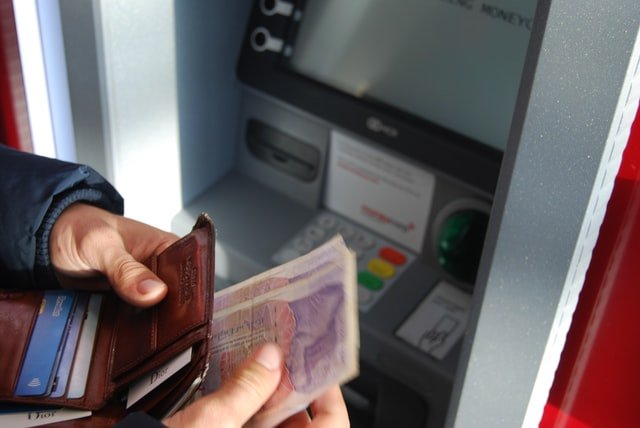 Hands pulling out bills from wallet in front of ATM